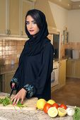 Arabian lady wearing hijab cutting veggies in the kitchen
