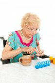 Disabled senior woman in wheelchair counting her pills into a pill container for the week.  White background.