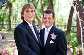 Handsome gay couple getting married under a floral archway, in outdoor ceremony.