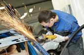 stock photo of wrecking  - professional repairman worker in automotive industry grinding metal body car with sparks - JPG
