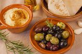 Bowl of olives with hummus and pita bread
