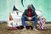Постер, плакат: Молодой человек с отношением сидел с шарфом над его рот замаскировать себя на граффити cla