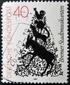 A stamp printed in Germany shows cartoon drawing of trotamusicos