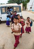 THANJAVUR, INDIA - FEBRUARY 14: unidentified School children get off the bus February 14, 2013 in Thanjavur, India. Indian government lays emphasis to primary education up to the age of fourteen years.