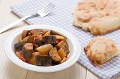 Cooked Stewed Eggplants In Plate Served With Bread On Table