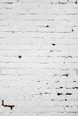 Old weathered white painted brick wall close up.