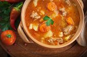 stock photo of hungarian  - Delicious veal stew soup with meat and vegetables on wood - JPG