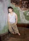 stock photo of runaway  - Barefoot boy leaning against the wall of a stairwell landing in an old building - JPG