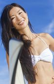 Beautiful young Hawaiian Asian woman surfer girl in bikini with surfboard standing in the surf on a beach