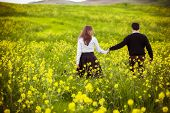foto of anonymous  - Young couple taking a walk on beautiful flower field - JPG