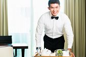 stock photo of waiter  - Asian Chinese room service waiter or steward serving guests food in a grand or luxury hotel room - JPG