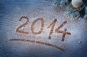 New Year 2014 on snow-covered wooden desk.