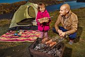 Child and her father are cooking grilled shish kebab outdoor