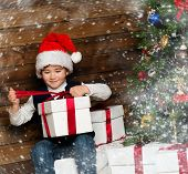Little boy in Santa hat opening gift box under christmas tree in wooden house interior