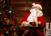 Santa Claus talking over phone in wooden home interior