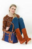 stock photo of platform shoes  - sitting woman wearing fashionable platform brown shoes with a handbag - JPG