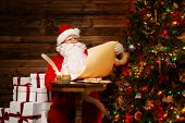 picture of nicholas  - Santa Claus in wooden home interior reading wish list scroll - JPG
