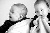 picture of fraternal twins  - Two redhead twin boys smiling and laughing on white - JPG