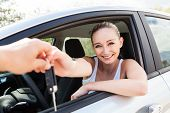 image of rental agreement  - young smiling woman sitting in car taking key handover rent purchase - JPG