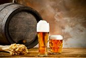 Beer keg with glasses of beer and blur background