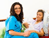 pic of kindness  - Smiling nurse caring for kind elder patient in nursing home.