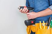 Close up mid section of a handyman with drill and tool belt by the wall