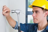 Close up of a serious young handyman hammering nail in wall