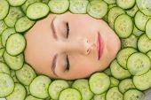 picture of cucumber slice  - Close up of a young beautiful woman with facial mask of cucumber slices on her face at spa salon - JPG