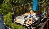 Women Sunbathing Beside Pool