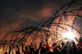 stock photo of human rights  - the barbed wire with clouds and sunblades - JPG