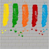 spots of varicoloured paint on a gray brick wall