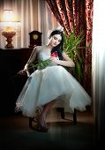 stock photo of lace-curtain  - Young beautiful luxurious bride sitting holding a red rose in classic scenery - JPG