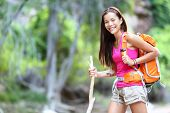 Asian hiking woman portrait. Female hiker in forest standing with walking stick looking at camera.
