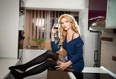 Attractive sexy blonde female with bright blue blouse and black stockings posing holding a glass
