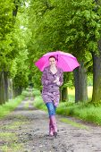 woman wearing rubber boots with umbrella in spring alley