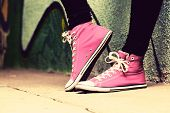 Close up of pink sneakers worn by a teenager. Grunge graffiti wall, concepts of teen rebel, problems of the youth, drugs, alcohol.