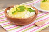 Bowl of tasty cottage cheese with pineapple on wooden table