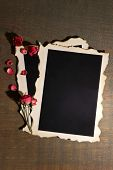 Blank photo paper and beautiful pink dried roses on wooden background