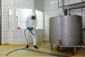 worker in white protective uniform,mask,gloves  with high pressure washer at  large industrial proce