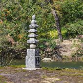 A small stone pagoda behind the Kyoko-chi (mirror pond) at Kinkaku-ji Temple