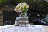 pic of mason  - Flowers in mason jar on a white table cloth - JPG