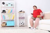 Lazy overweight male sitting on couch with chips and watching television