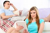 Loving couple  relaxing with laptop  and tablet, on home interior background