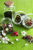 Assortment of herbs and tea in glass jars on wooden background