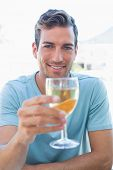 Portrait of a smiling young man holding wine glass