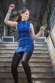 stock photo of underpass  - Pretty young girl dancing in railroad station underpass - JPG