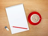 Blank notepad with office supplies and red coffee cup on wooden table. Above view