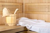stock photo of sauna  - Traditional wooden sauna for relaxation with bucket of water and set of clean towels - JPG