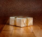 Gift Box In Gold Wrapping Paper With Ribbon On Wooden Table