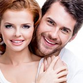 Closeup portrait of beautiful smiling couple posing at studio over white background.